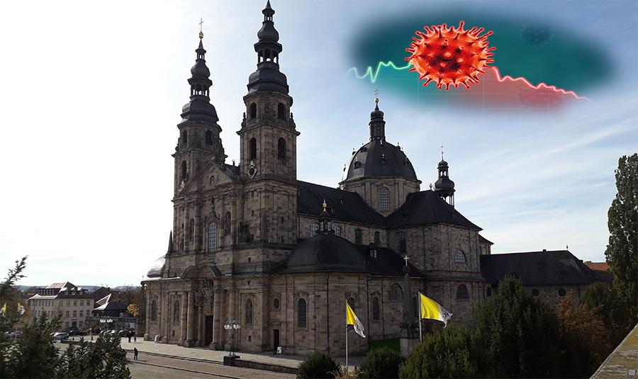 Über dem Fuldaer Dom schwebt eine Wolke mit dem Corona-Virus. Der Kern des Virus ist auf einem stagnierenden Graphen plaziert.