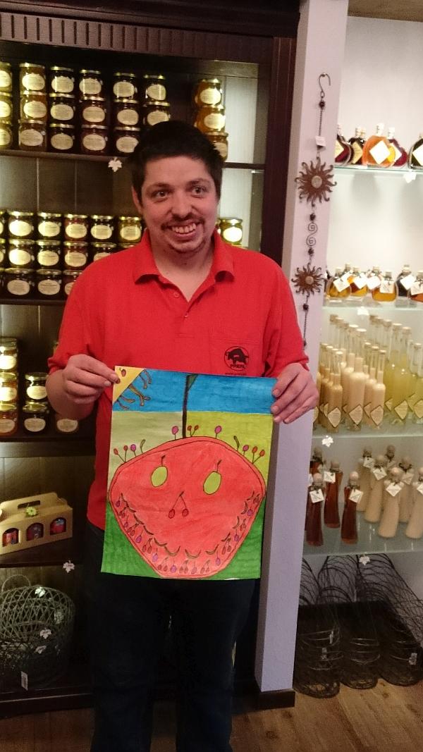 Helmut steht im Hofladen der Werkstatt und hält sein gemaltes Bild vor sich.