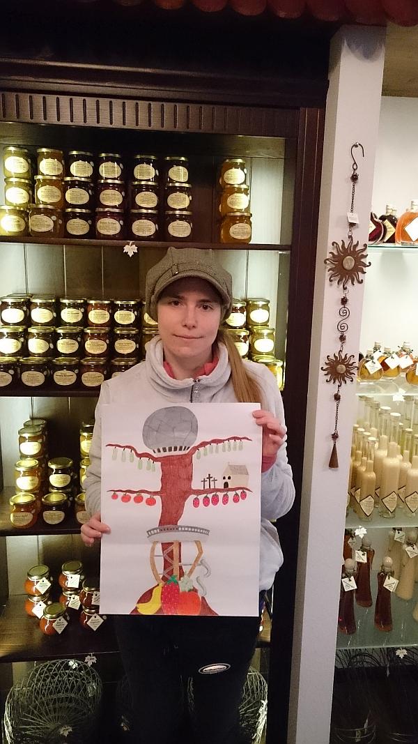 Sandra steht im Hofladen der Werkstatt und hält ihr gemaltes Bild vor sich.
